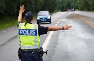 Poliskontroll: kvinnlig trafikpolis vinkar in bil